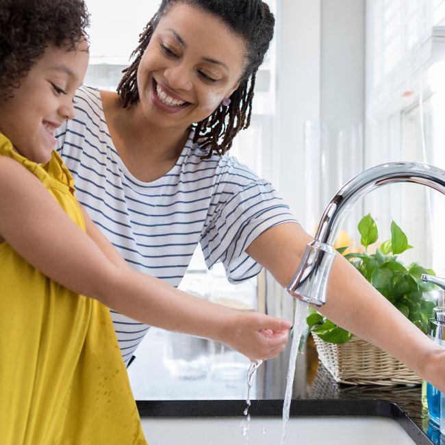mother and daughter washing hands on kitchen sink and smiling