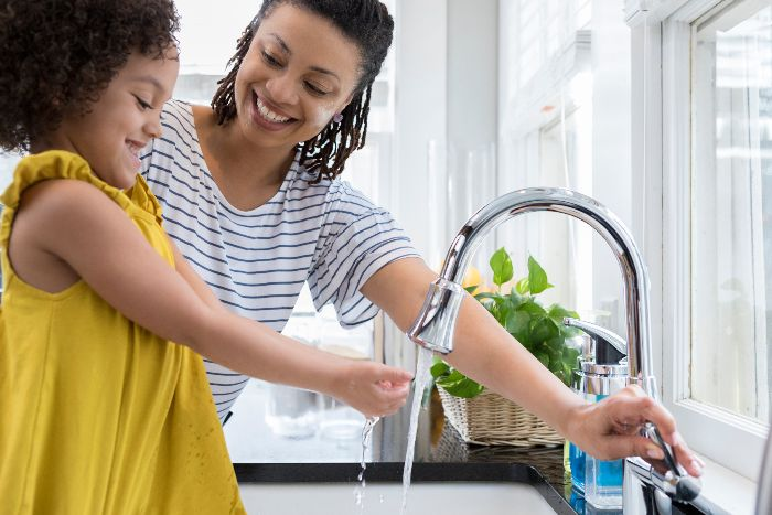 mother and daughter washing hands on kitchen sink happy